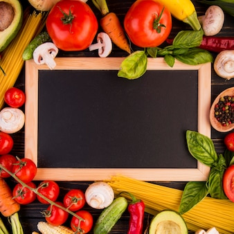 Top view assortment of different vegetables with empty blackboard
