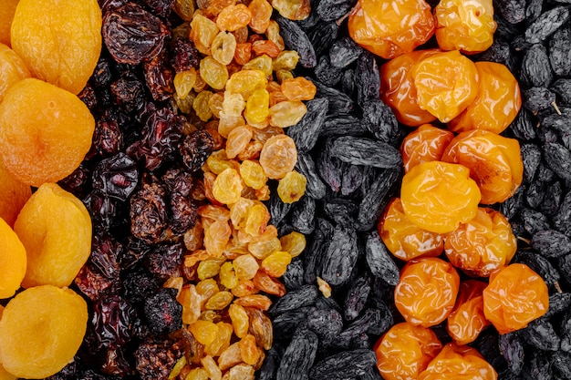 Top view of assortment of dried fruits apricots raisins cherries and cherry plums