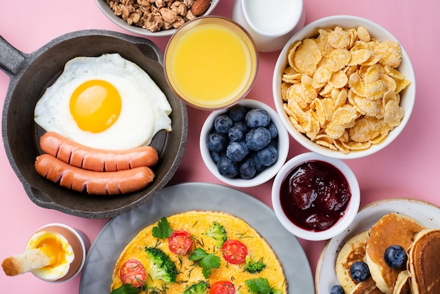 Top view of assortment of food with omelette and sausages