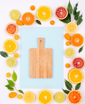 Top view assortment of fresh fruits with chopping board
