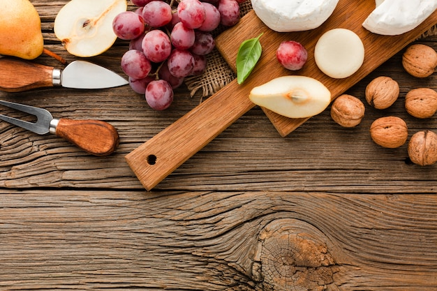 Top view assortment of gourmet cheese on wooden cutting board with grapes walnuts and ustensils