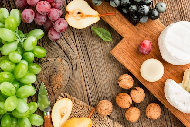 Top view assortment of gourmet cheese on wooden cutting board with grapes and walnuts