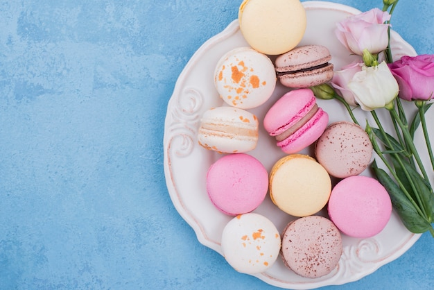 Top view of assortment of macarons on plate with roses