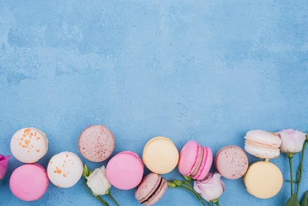 Vista dall'alto dell'assortimento di macarons con rose e copia spazio