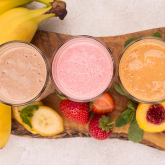 Top view of assortment of milkshakes with banana and peach