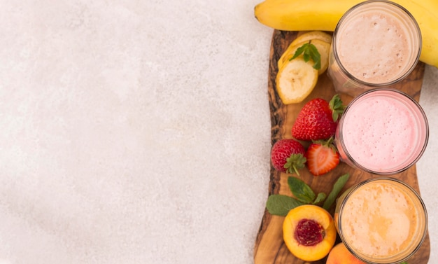 Top view of assortment of milkshakes with fruits and copy space