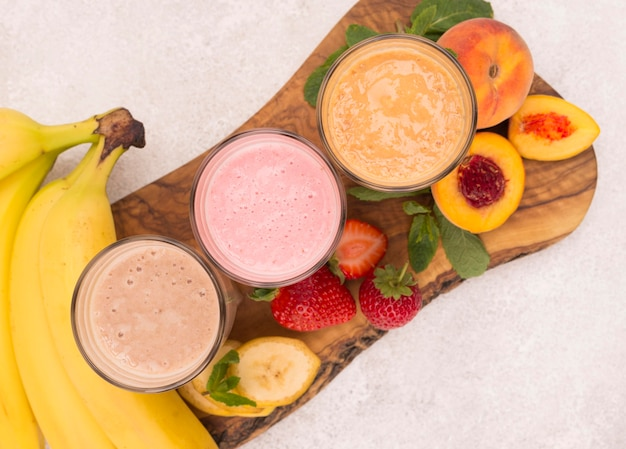 Top view of assortment of milkshakes with peach and banana
