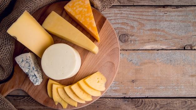 Вид сверху ассортимент вкусных сыров на столе