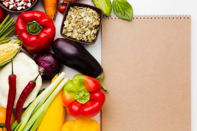 Вид сверху ассортимент разных овощей с пустым блокнотом