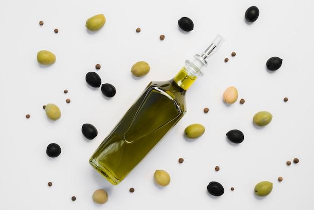 Вид сверху ассортимент оливок и бутылка масла