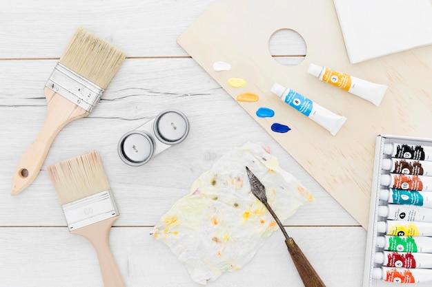 Вид сверху ассортимента расходных материалов для краски на столе
