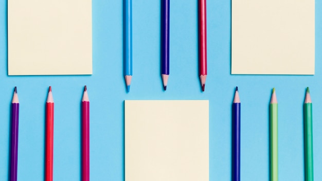 Вид сверху на ассортимент карандашей и бумажных заметок