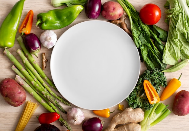 Ассортимент овощей с пустой тарелкой, вид сверху
