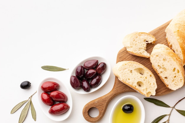 Top view assortment of olives bread slices and olive oil with copy space