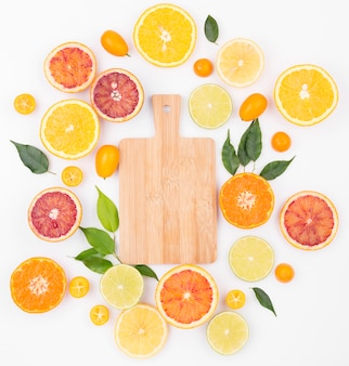 Top view assortment of organic fruits with chopping board