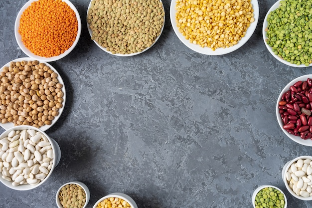 Top view of assortment of peas, lentils, beans and legumes over gray background.
