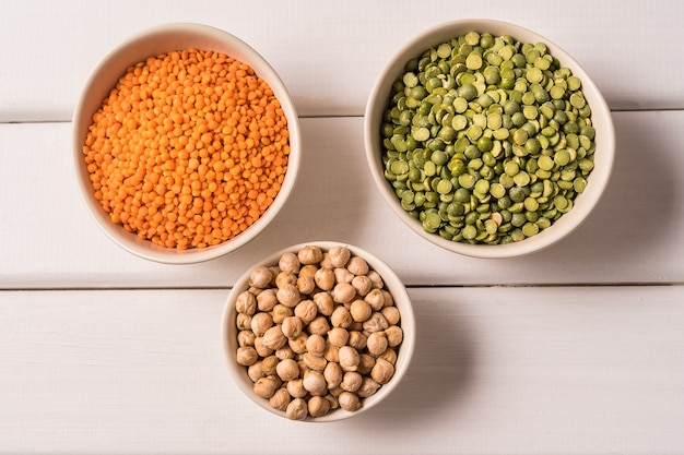 Top view of assortment of peas, lentils, beans and legumes on white