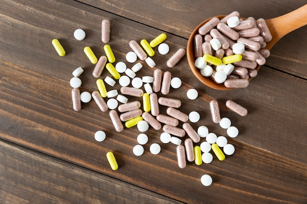 Top view of an assortment of pharmaceutical medicine pills, tablets and capsules on a dark wooden table.