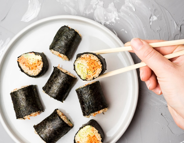 Top view assortment of sushi rolls with chopsticks