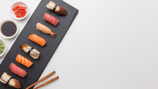Top view assortment of sushi with soy sauce and fresh ginger