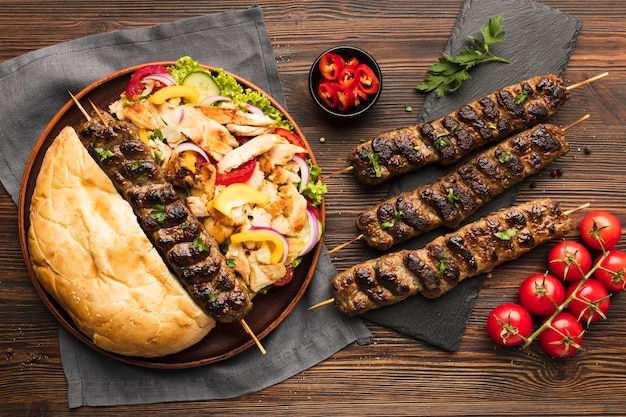 Top view of assortment of tasty kebabs with tomatoes and vegetables