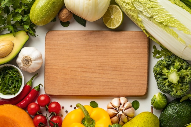 Top view of assortment of vegetables with chopping board