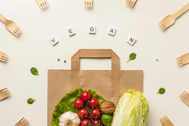 Top view of assortment of vegetables with paper bag and the word vegan