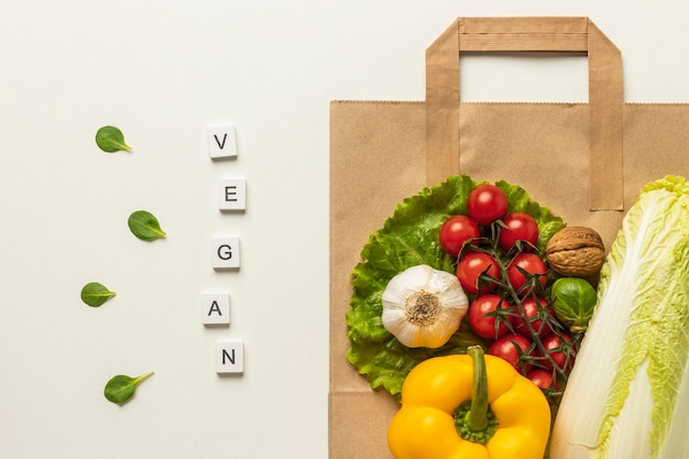 Top view of assortment of vegetables with the word vegan and paper bag