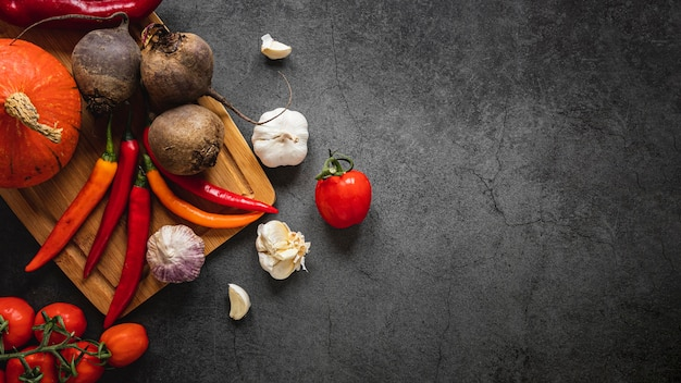 Top view assortment of veggies dark copy space background