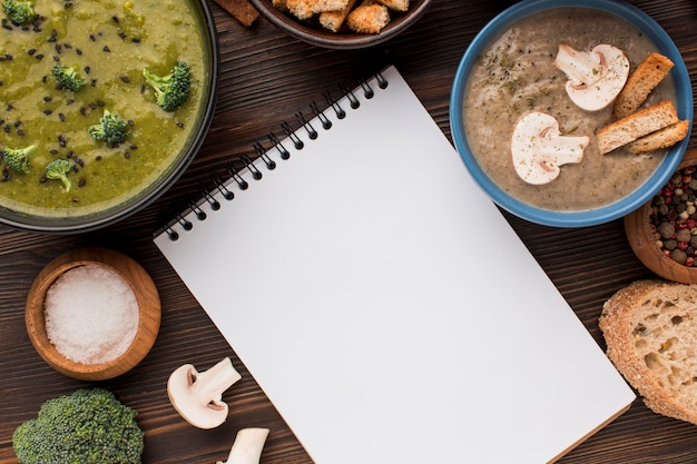 Top view of assortment of winter mushroom and broccoli soups with notebook