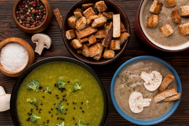 Top view of assortment of winter mushroom and broccoli soups