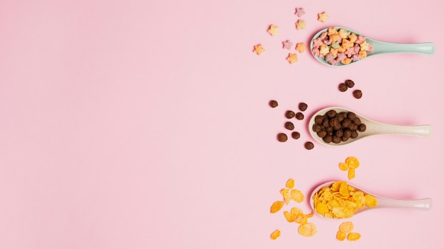 Top view assortment with spoons and cereals on pink background