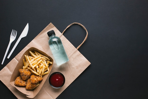 Top view assortment with unhealthy food and water