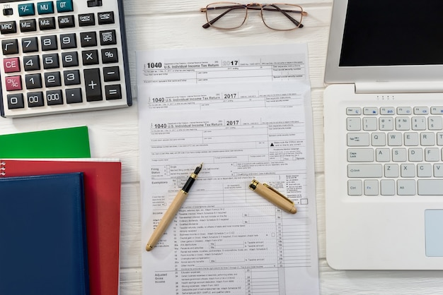 計算機のラップトップとメモ帳を備えた1040税務フォームの上面図