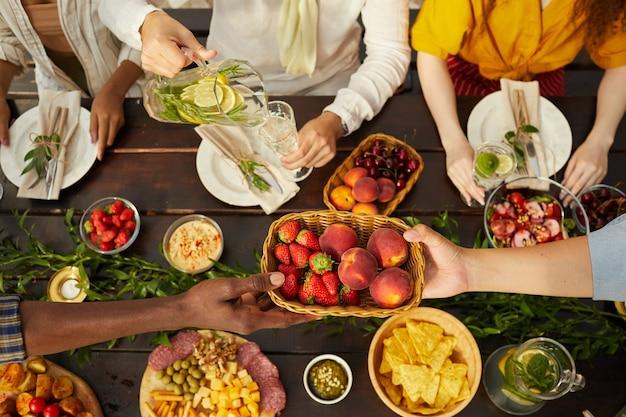 야외 여름 파티 동안 저녁 식사를 함께 즐기는 사람들의 다민족 그룹에서 상위 뷰, 나무 테이블에 걸쳐 신선한 과일과 열매를 나눠주는 손에 초점