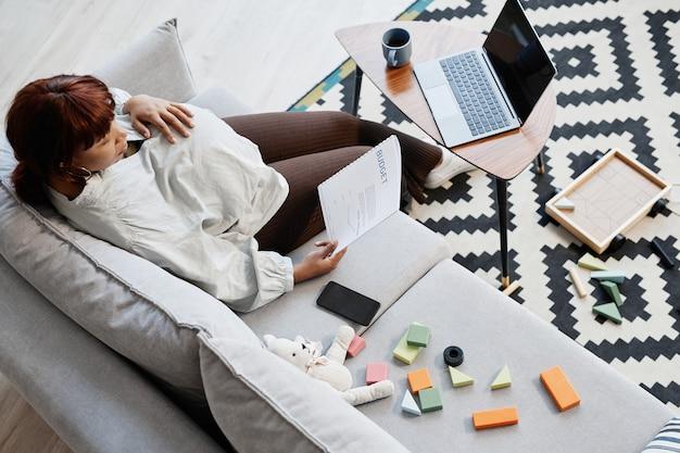 Вид сверху на беременную афроамериканку, читающую отчет о бюджете во время работы из дома в окружении игрушек, место для копирования