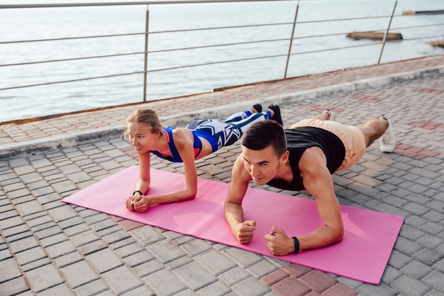 Top view of athlete sportive couple doing plank, training together on the quay