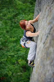 Top view of athletic woman climbing steep cliff wall