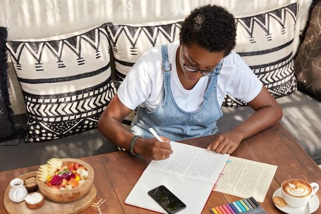 La vista superiore della donna nera alla moda attraente scrive la revisione del libro nel blocco note