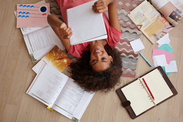Vista dall'alto di attraente giovane femmina riccia con la pelle scura sdraiato sul tappeto mentre legge le note, si prepara per gli esami con molti libri, indossa la maglietta rosa