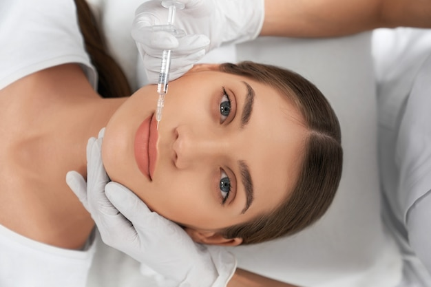 Top view of attractive young woman on procedure augmentation lips in beautician