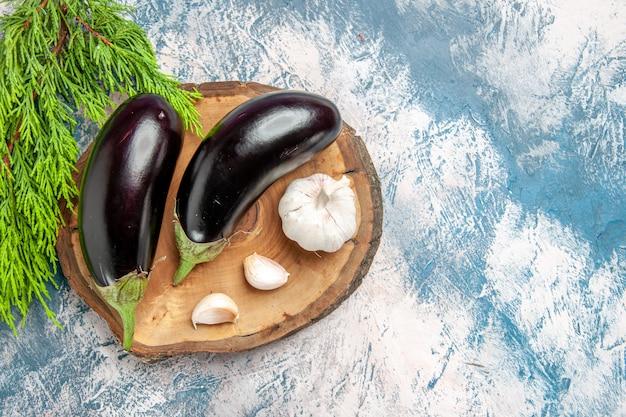 Vista dall'alto melanzane aglio su tavola di legno dell'albero su sfondo blu-bianco