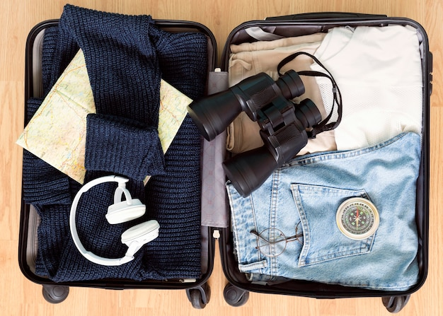 Top view autumn adventure elements in luggage