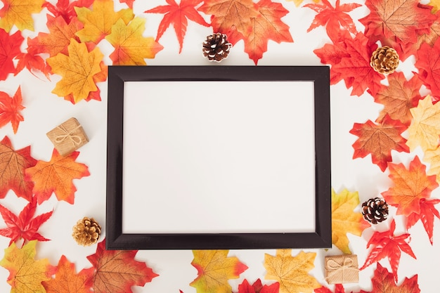 Top view autumn colorful maple leaves, cones, gift box and blank  frame on white