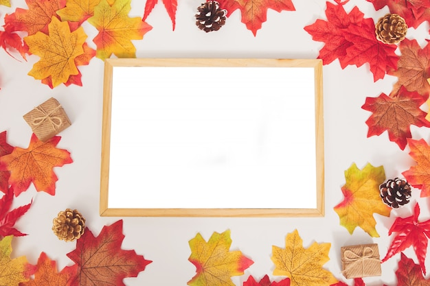 Top view autumn colorful maple leaves, cones, gift box and  wooden surface frame on white