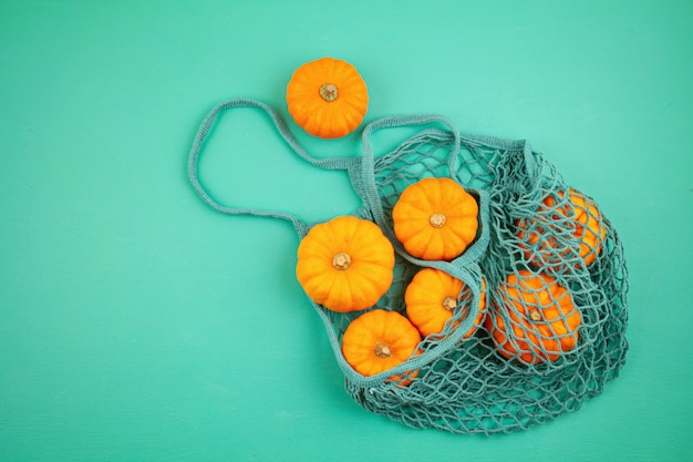 Top view autumn composition with pumpkins in mesh shopping bag on turquoise background