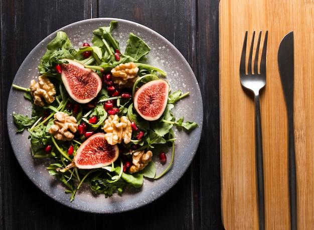 Vista dall'alto di insalata di fichi d'autunno su piatto e posate