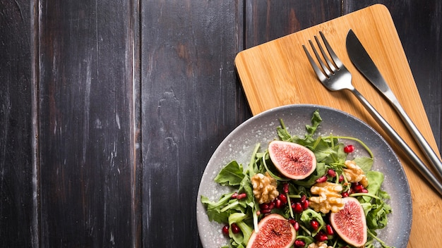Top view of autumn fig salad on plate with cutlery and copy space