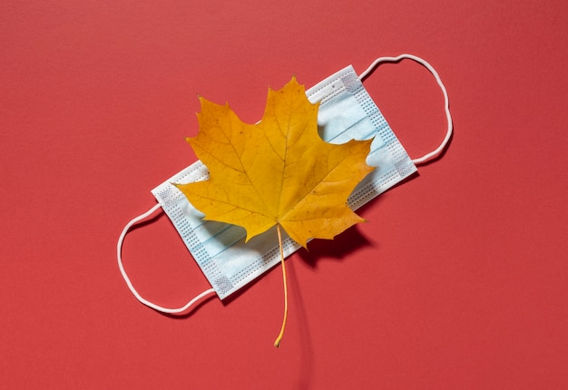 Top view of autumn leaf with medical mask