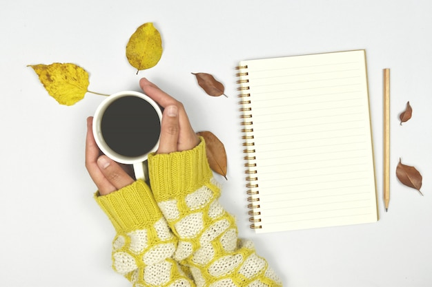 Top view of autumn leaves with coffee and notebook